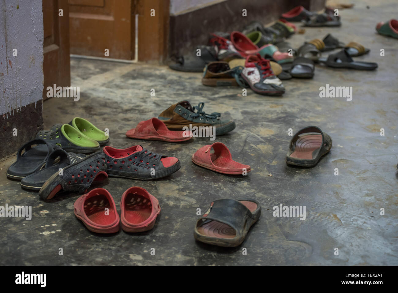 Assorted shoes abandoned by the young monks attending their classes. Buddhist artifacts and symbolism in Dirang - Stock Image