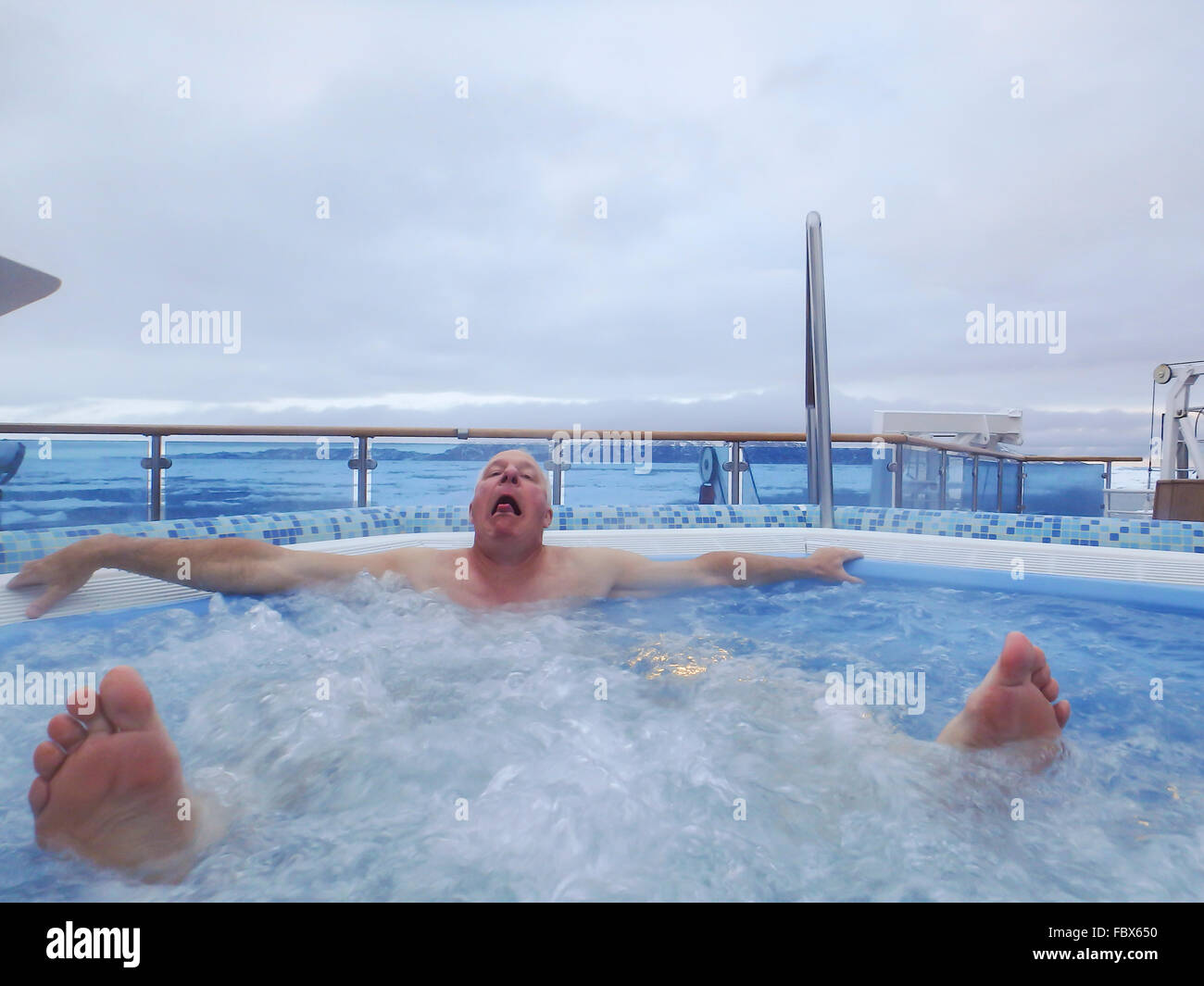 Man grimacing in hot tub on cruise ship in ice field of Antarctica. - Stock Image