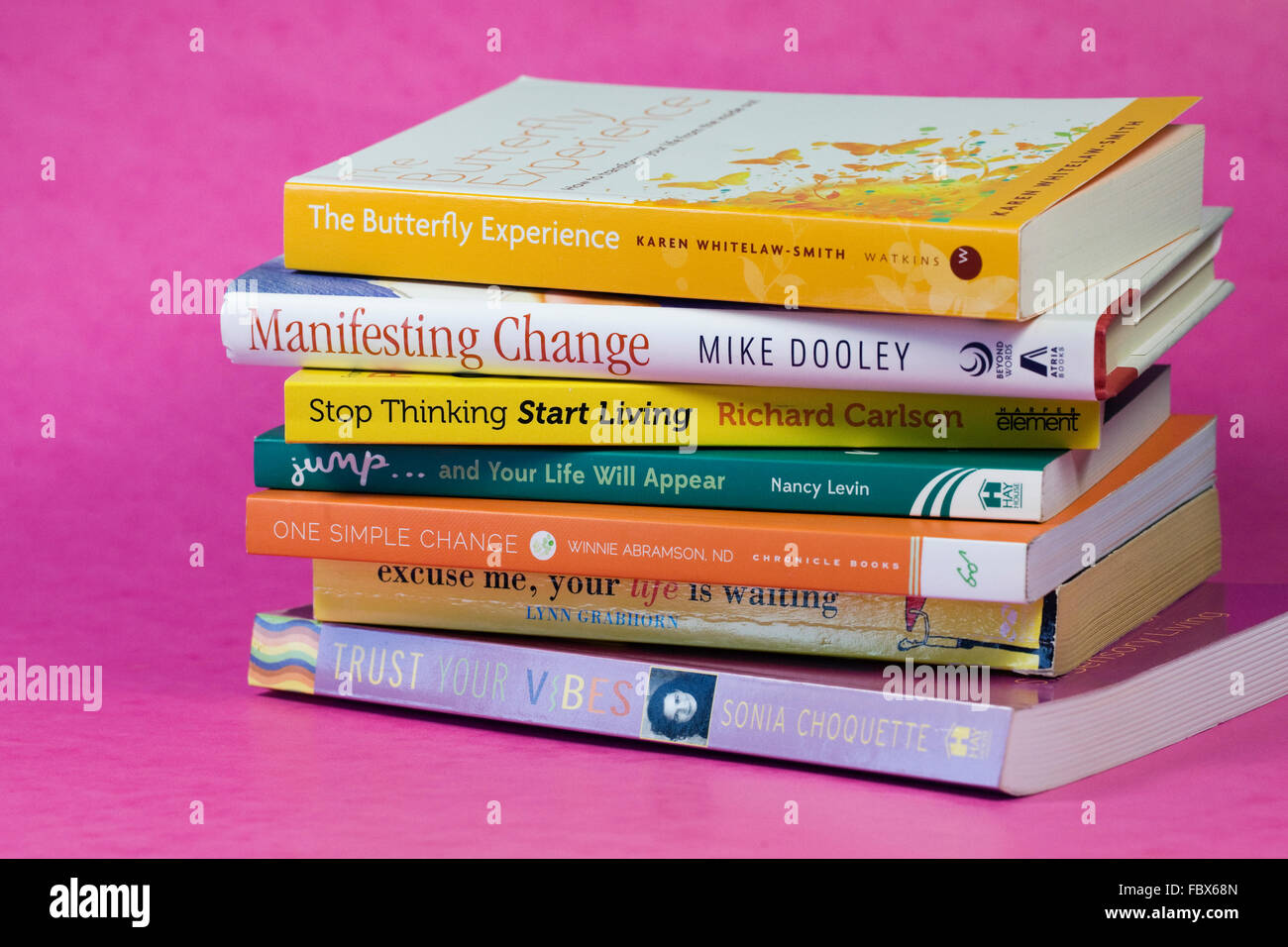 A pile of self help books on a pink background. - Stock Image