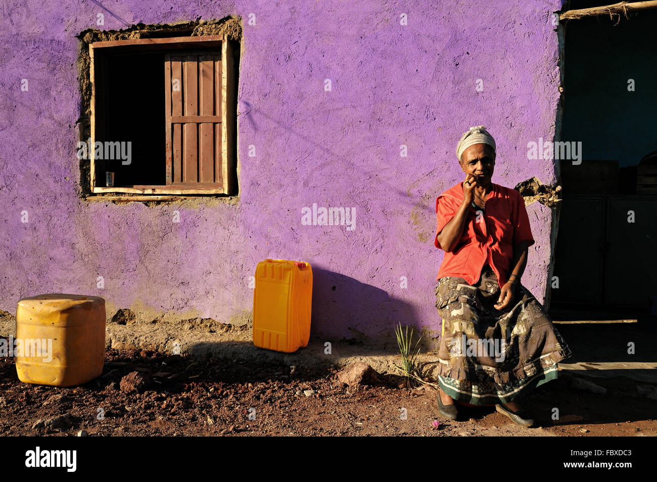 African mature woman sitting in front of her house in Logia (Logiya), Afar Region, Ethiopia Stock Photo