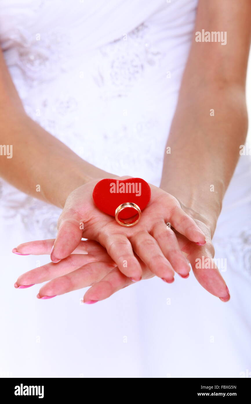 Female hands of bride in white dress with engagement or wedding ring ...