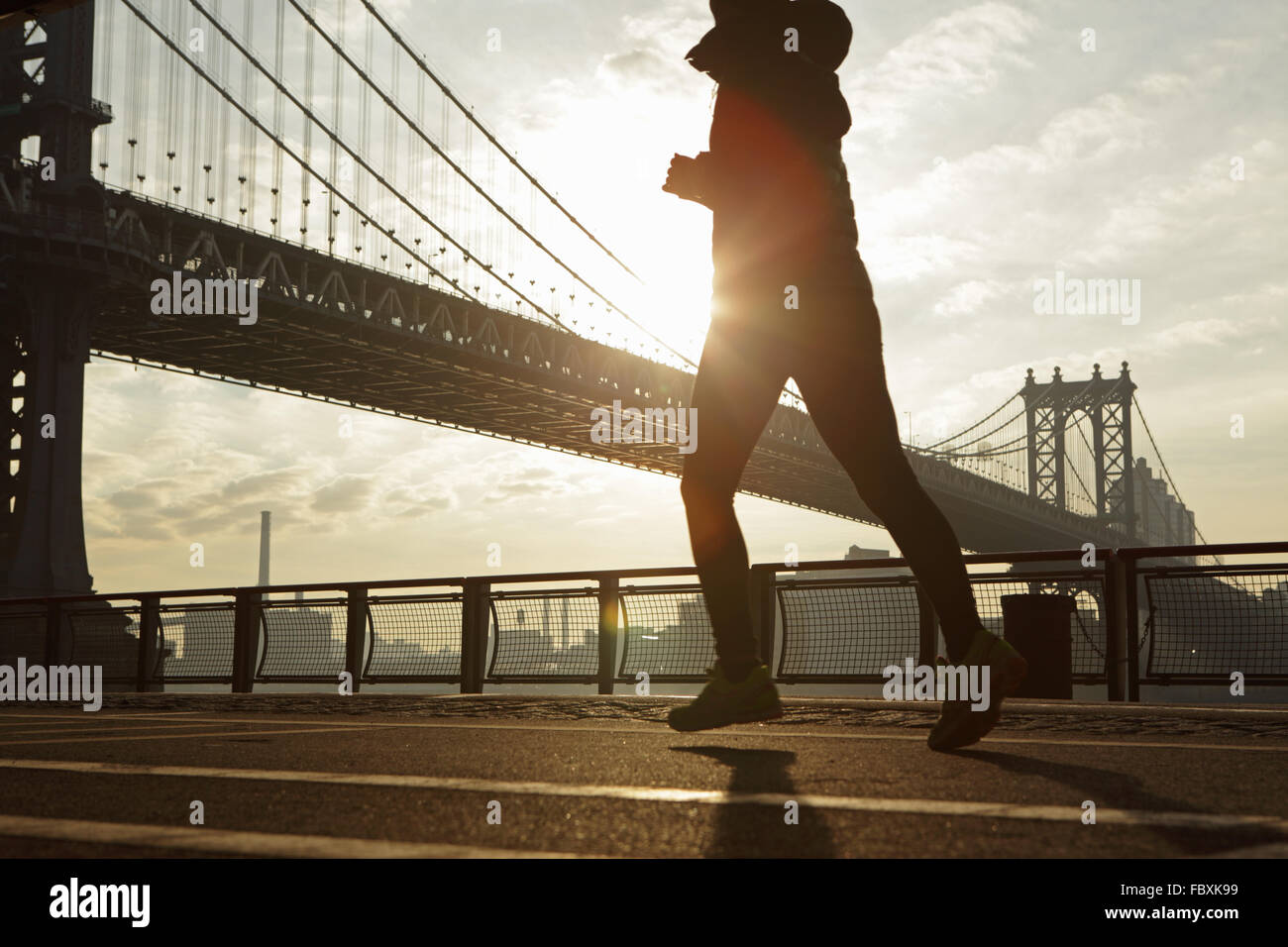 Sunrise over the Manhattan Bridge New York City morning as a jogger runs north up the East River Esplanade - Stock Photo