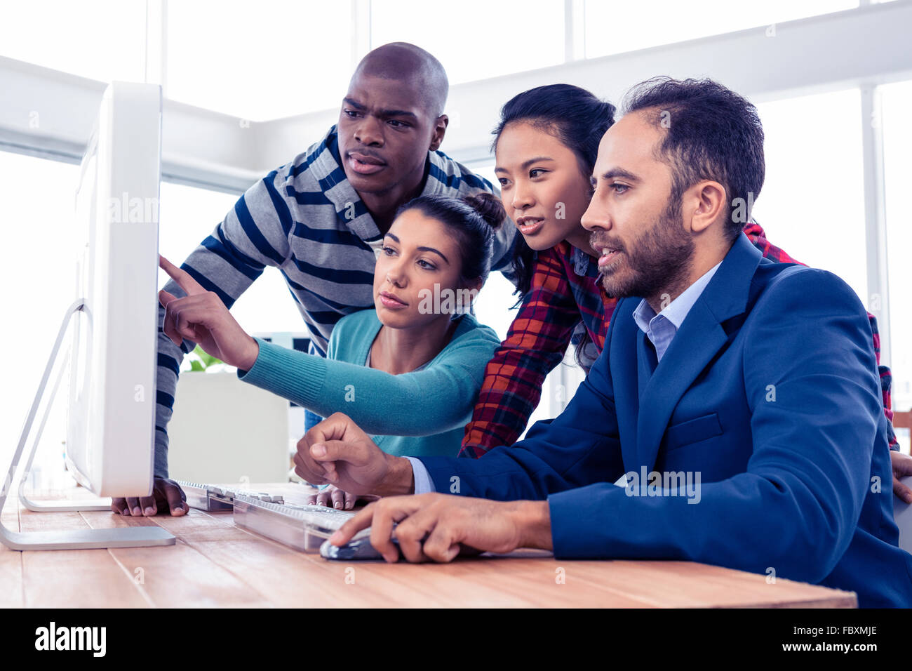 Businesswoman explaining colleagues over computer Stock Photo