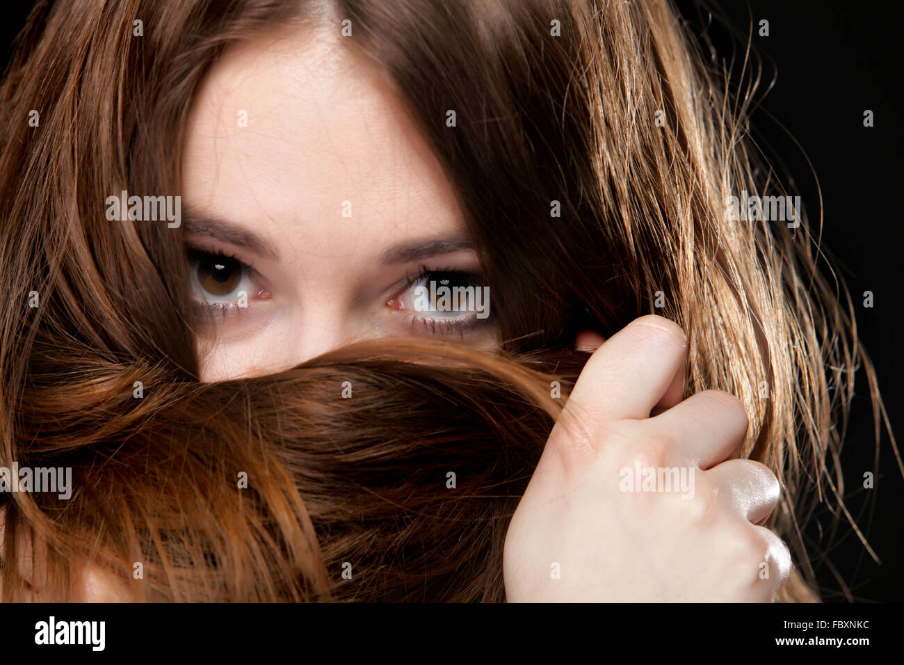 Closeup woman covers the face by long brown hairs Stock Photo