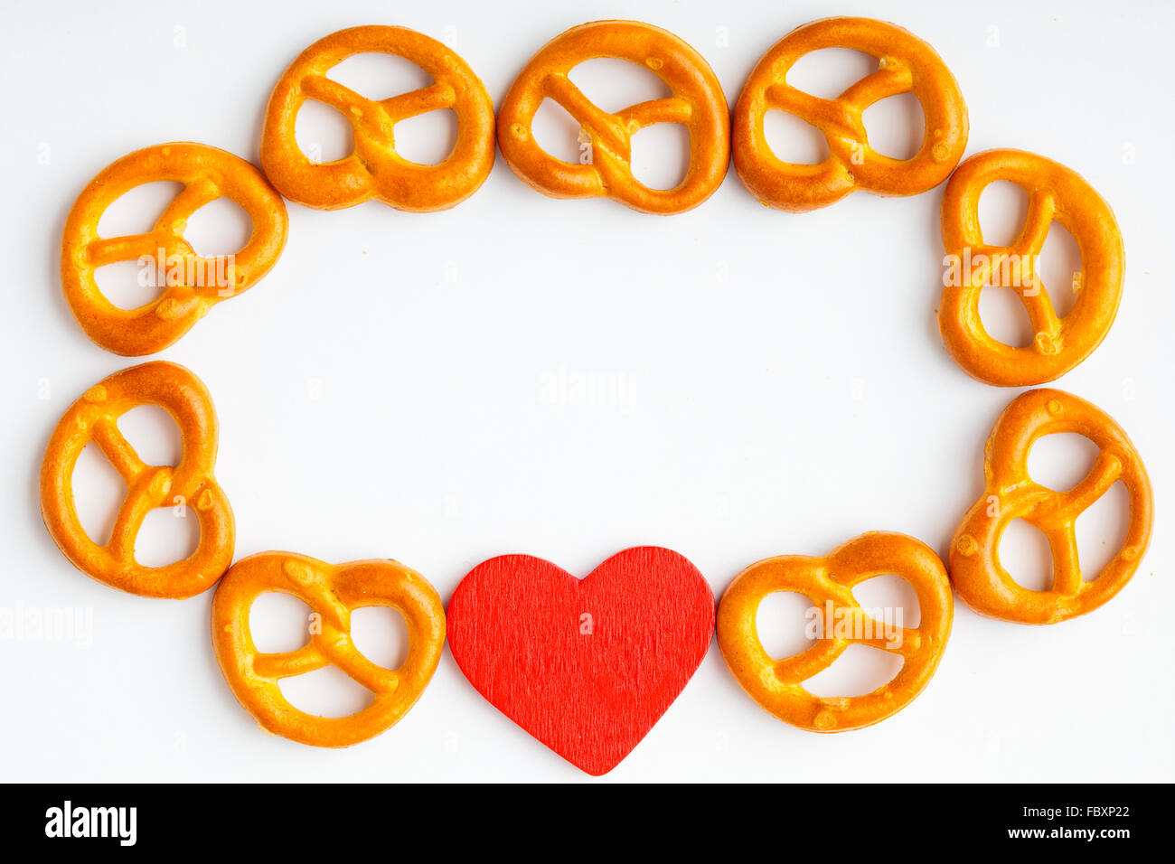Frame Of Pretzels And Red Heart White Background Stock Photo