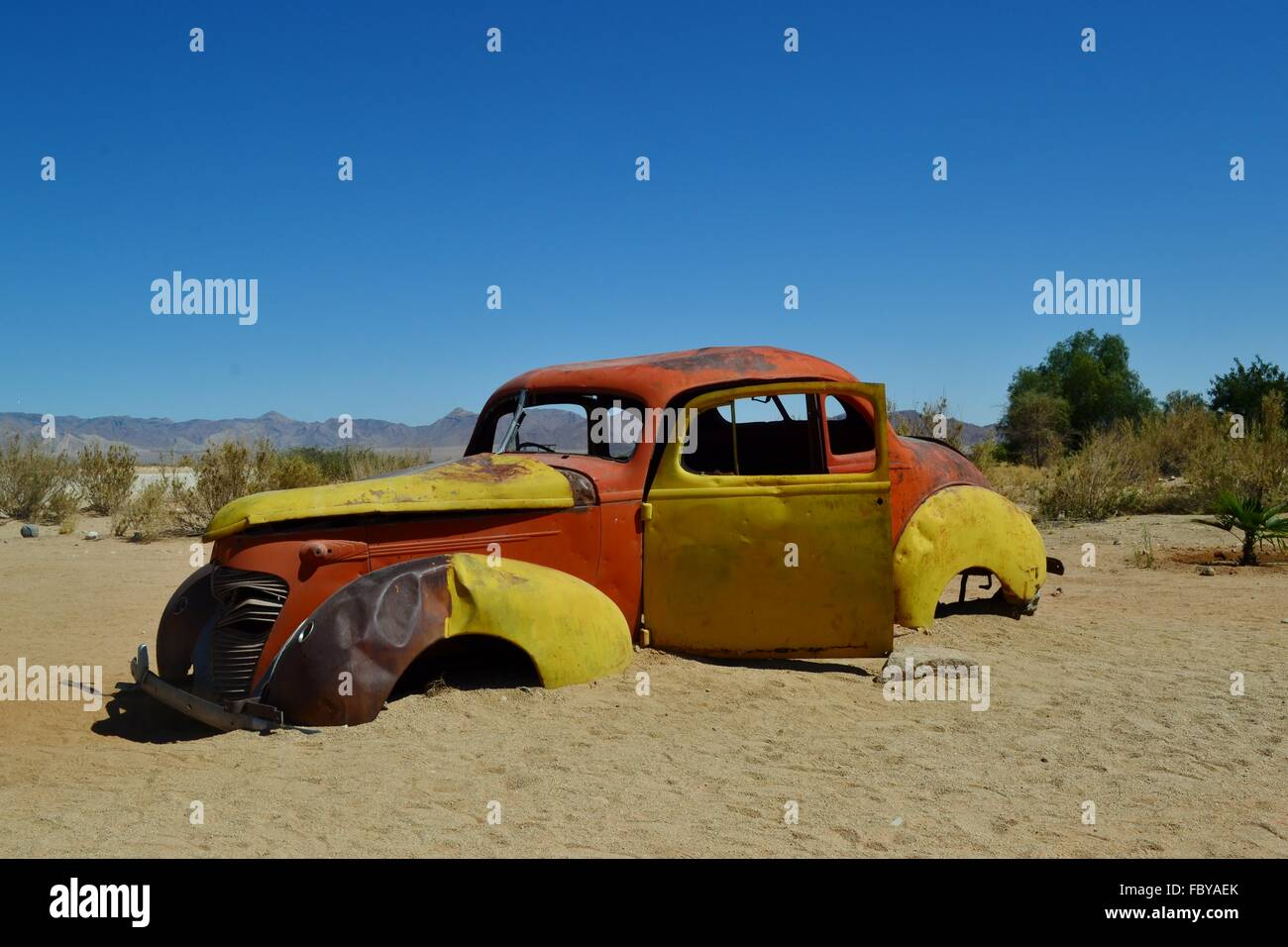 Abandoned, rusting and broken down old car in a desert - Stock Image