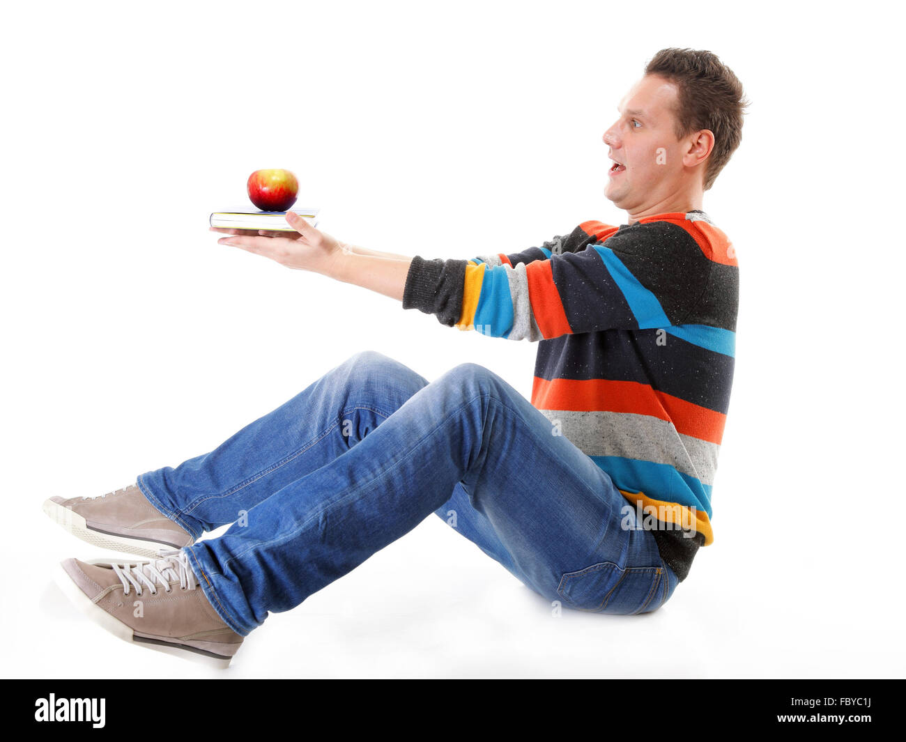 Man holding a book and one red apple full body - Stock Image