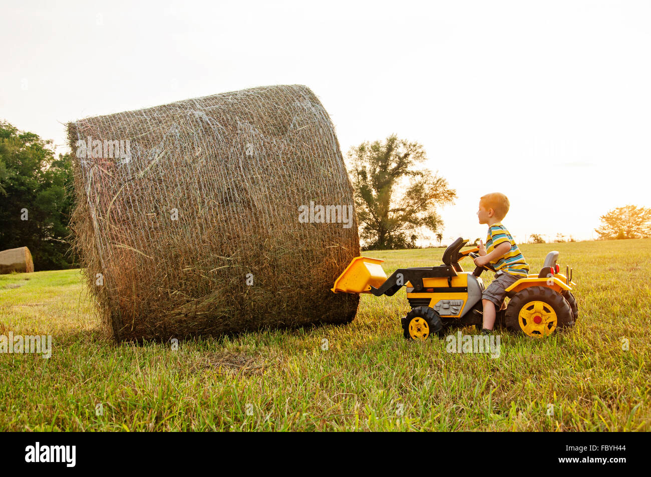 child using bucket on toy tractor to lift bale of hay - Stock Image
