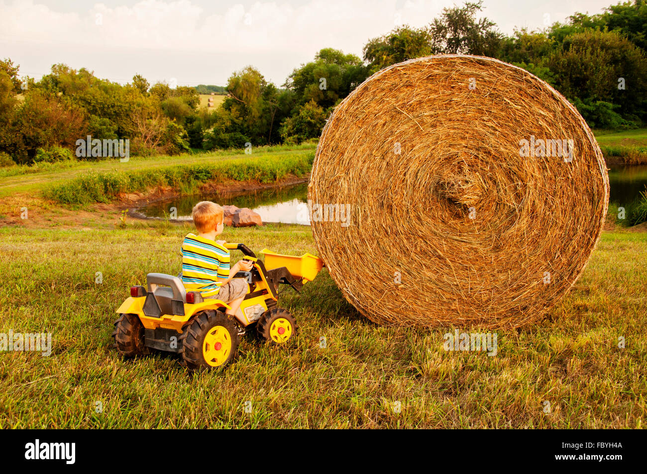 boy trying to lift haybale with  bucket on toy tractor - Stock Image