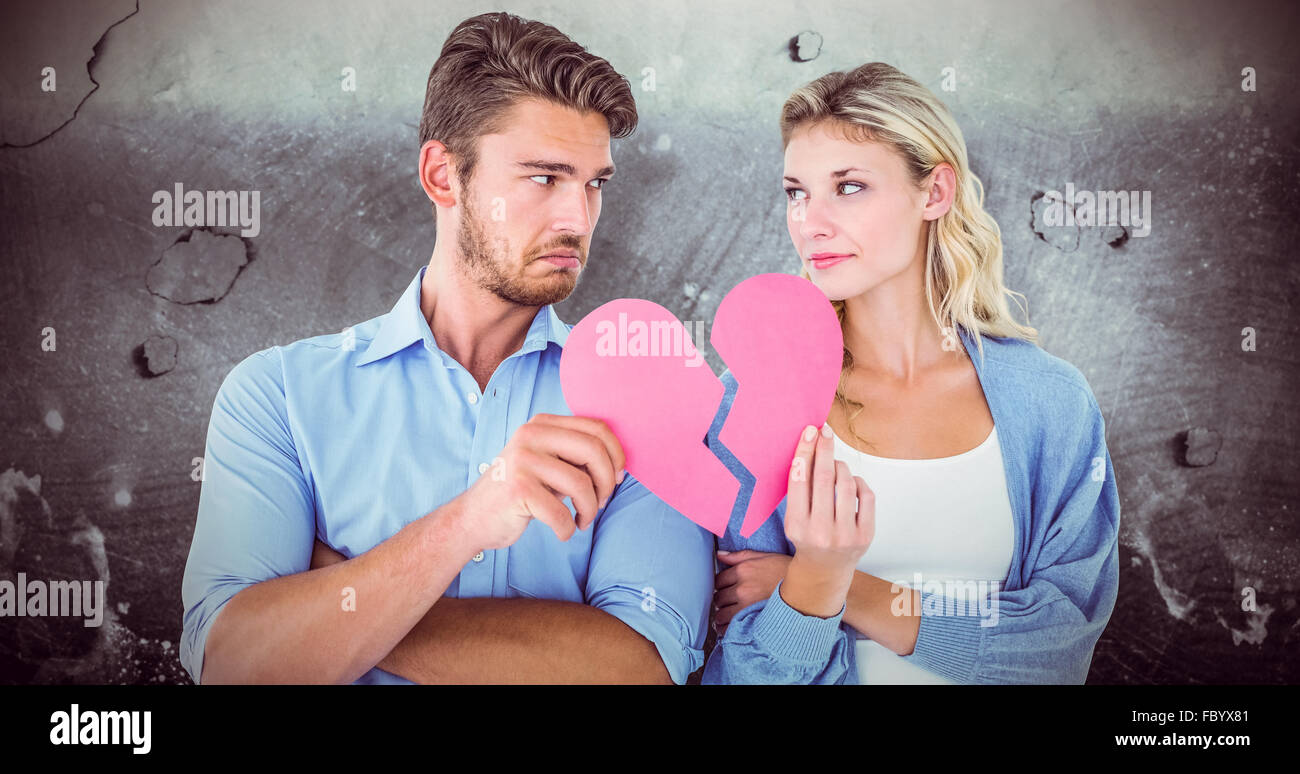 Composite image of couple holding two halves of broken heart - Stock Image