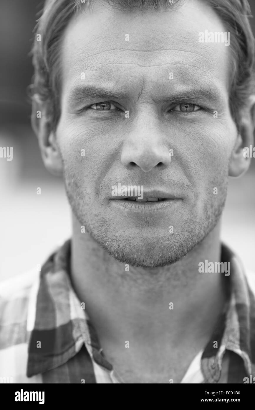 Black and white portrait of man in a checkered shirt. Outdoor shoot - Stock Image