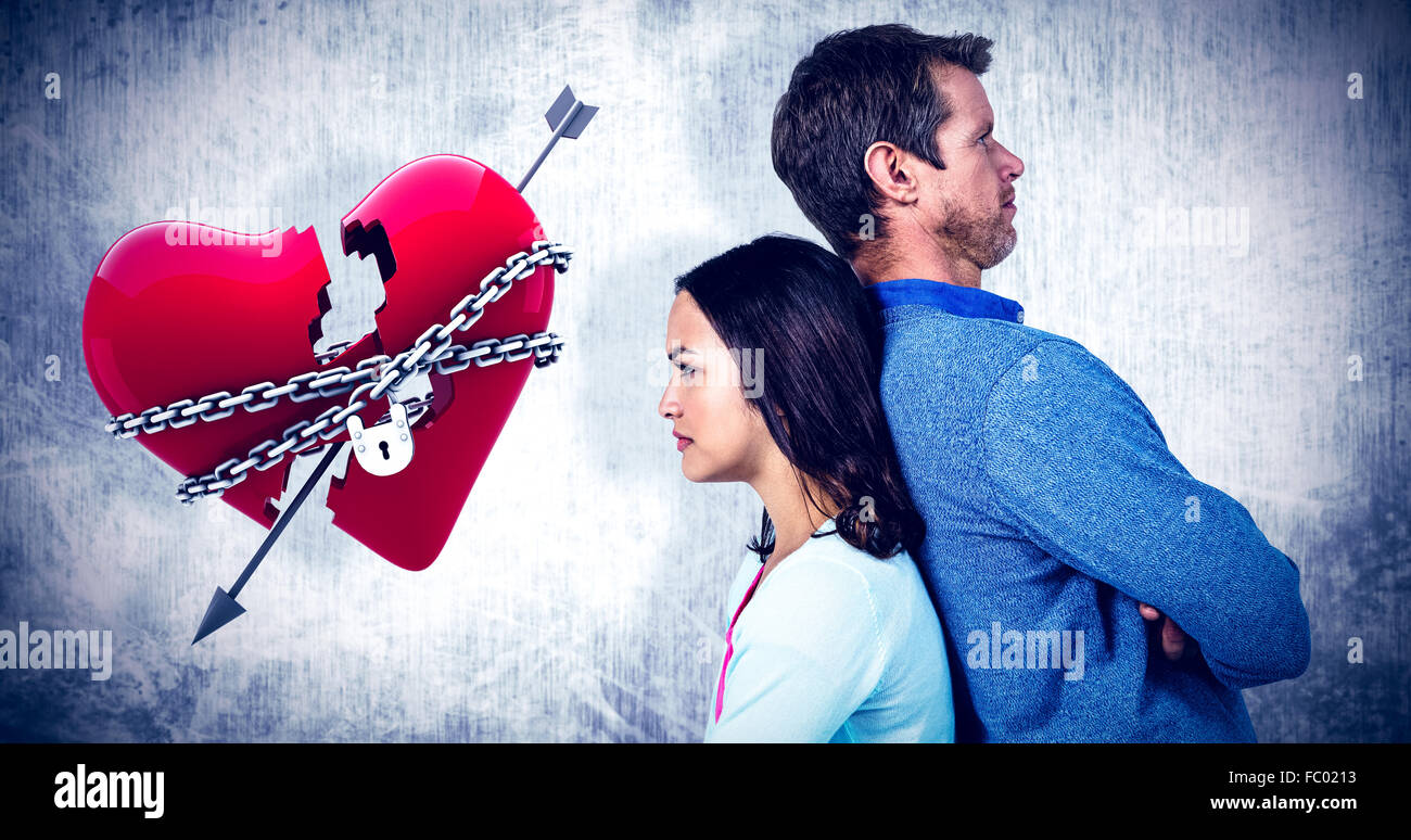 Composite image of angry couple standing back to back - Stock Image
