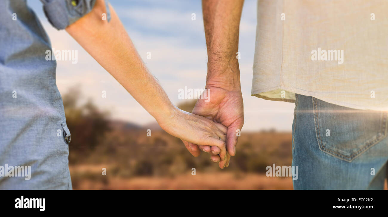 Composite image of couple holding hands in park - Stock Image