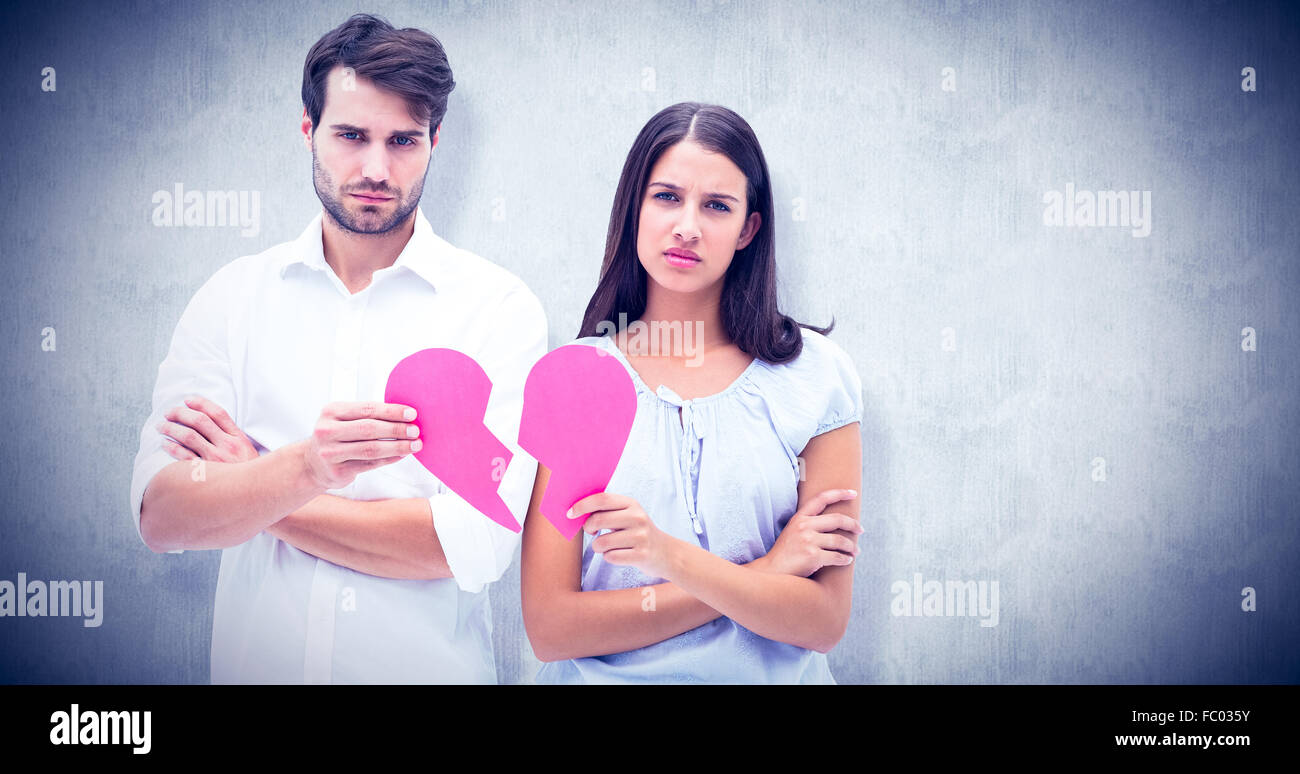 Composite image of upset couple holding two halves of broken heart - Stock Image