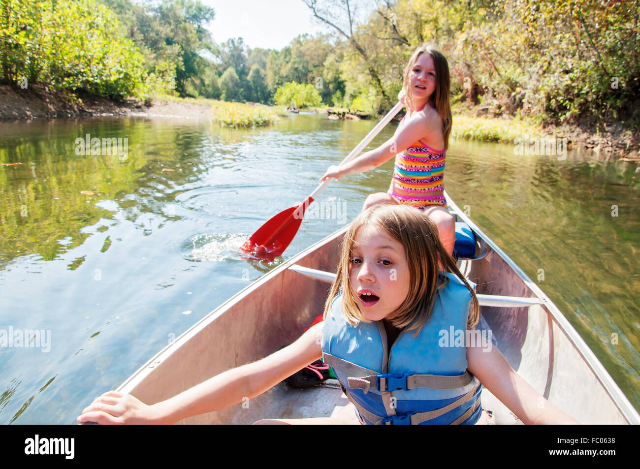 girls rowing canoe down river - Stock Image