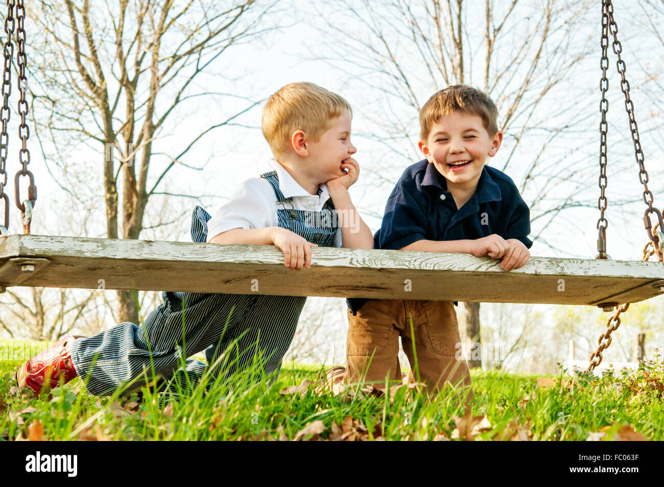 Two boys leaning on swing laughing together - Stock Image