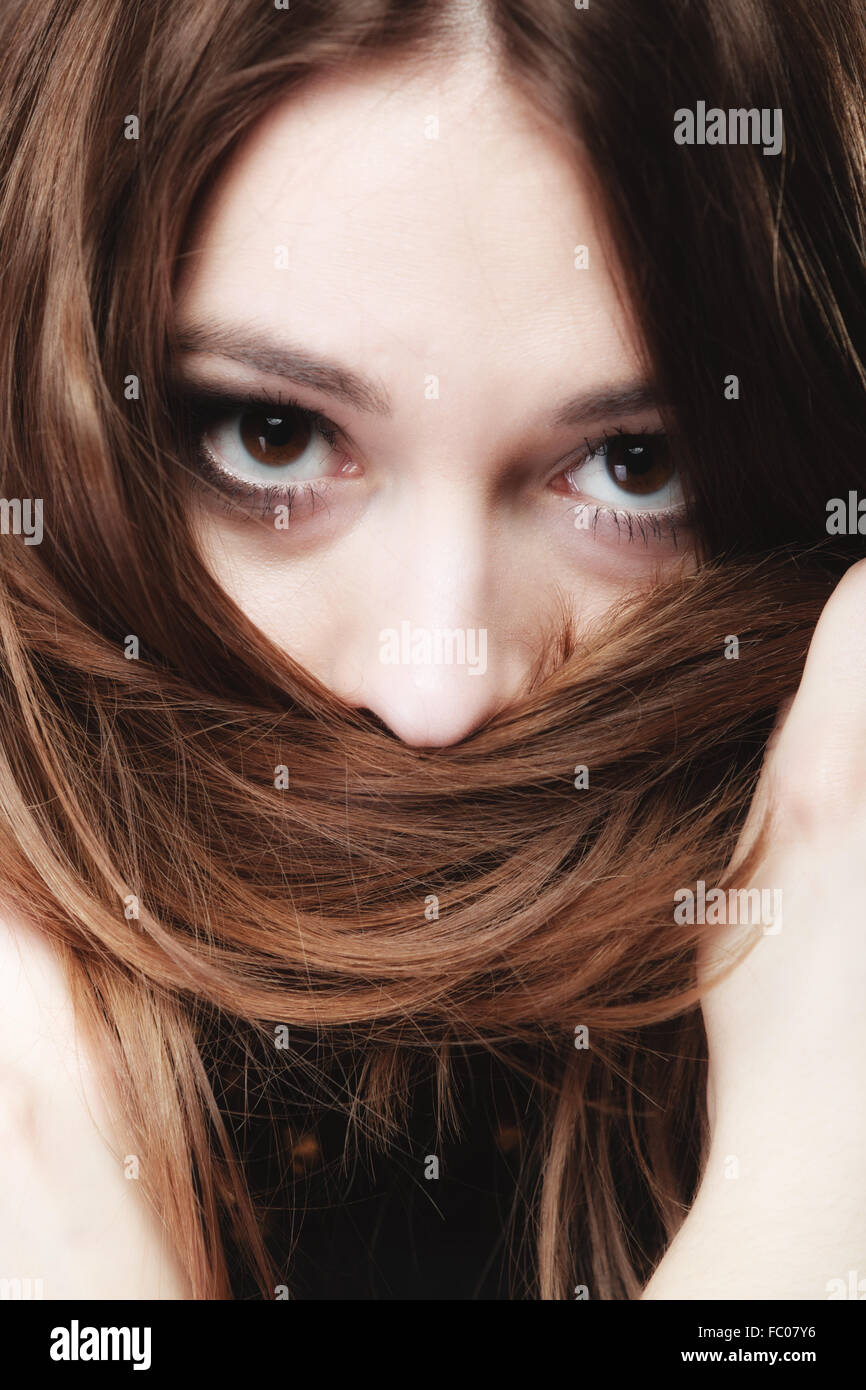 woman covers the face by long brown hairs Stock Photo