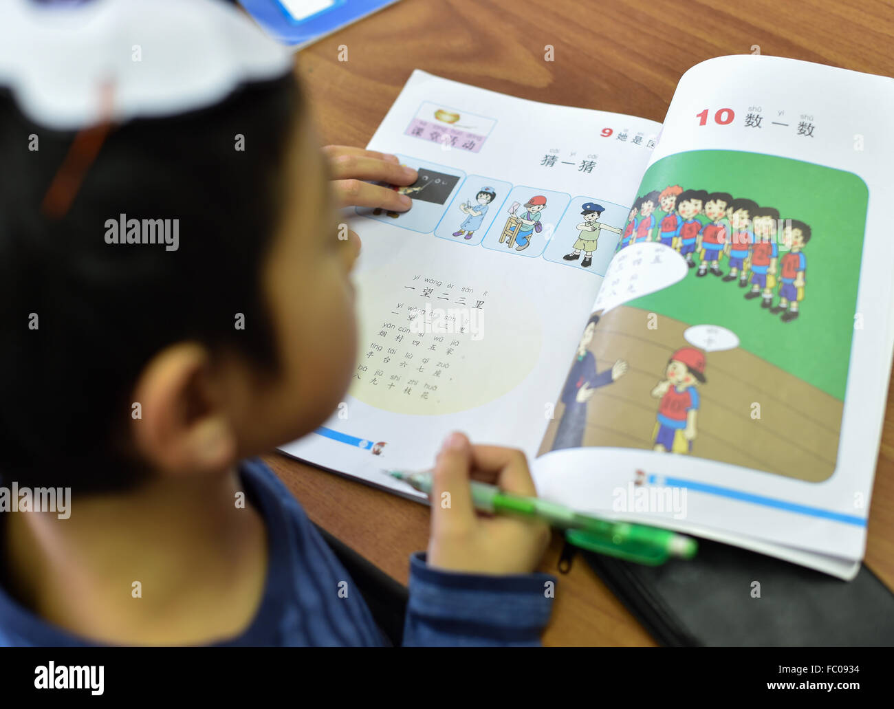 Oberursel, Germany. 22nd Nov, 2015. Annette Feil looks at a school book on the entry-level course at the International - Stock Image
