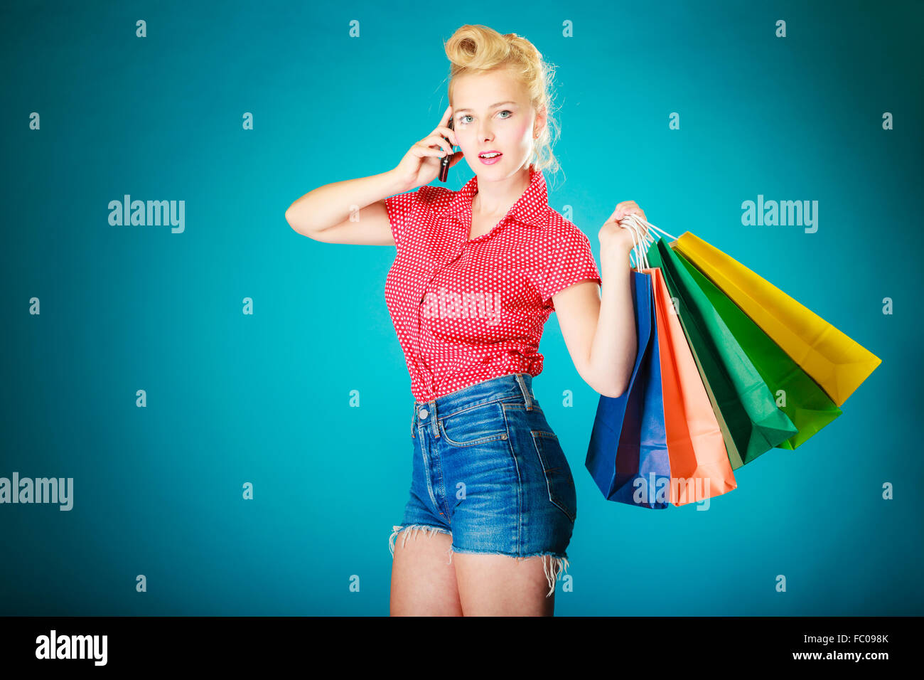 Pinup girl with shopping bags calling on phone - Stock Image