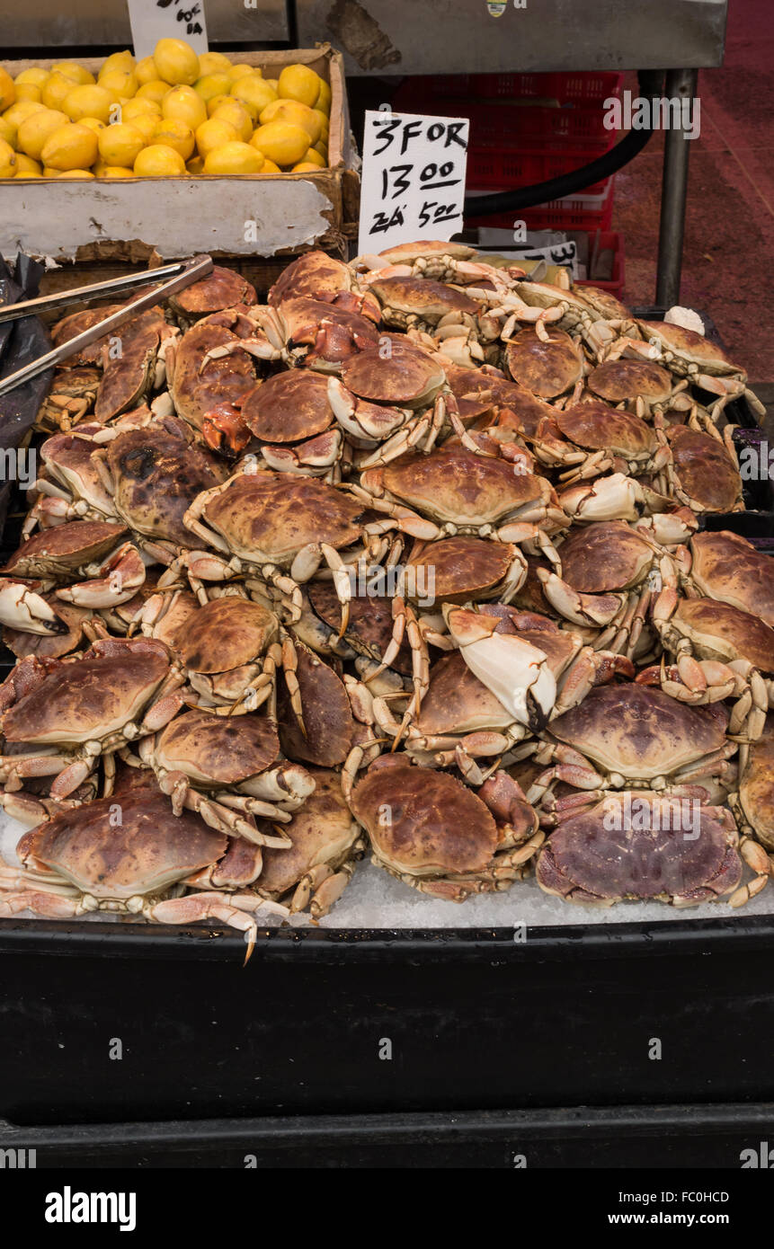 Piles of crabs and lemons for sale in a seafood and fish market shop in Chinatown, New York City. - Stock Image