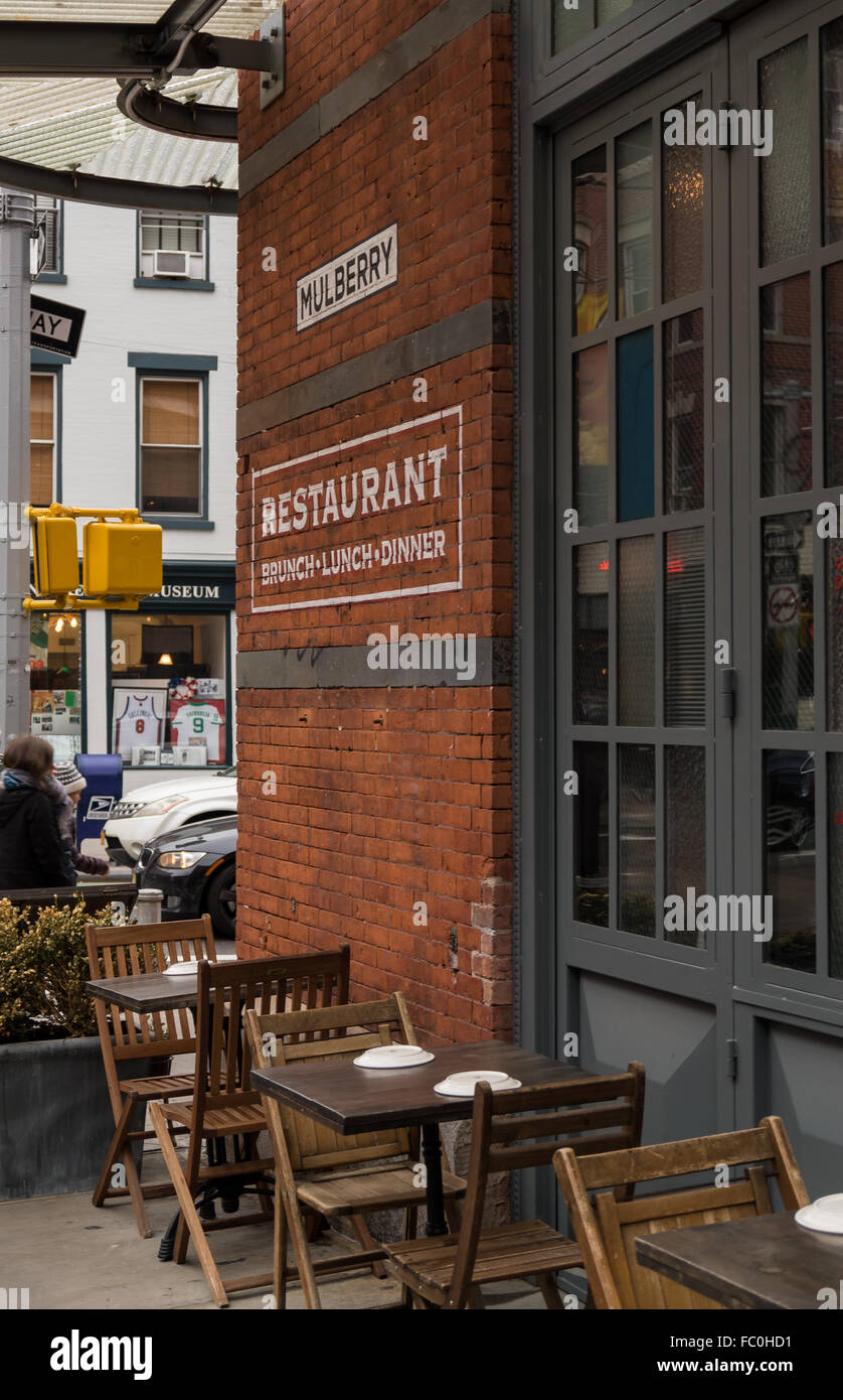 Exterior of Gelso and Grand, with dining tables for al fresco dining and painted signs on the red brick wall. - Stock Image