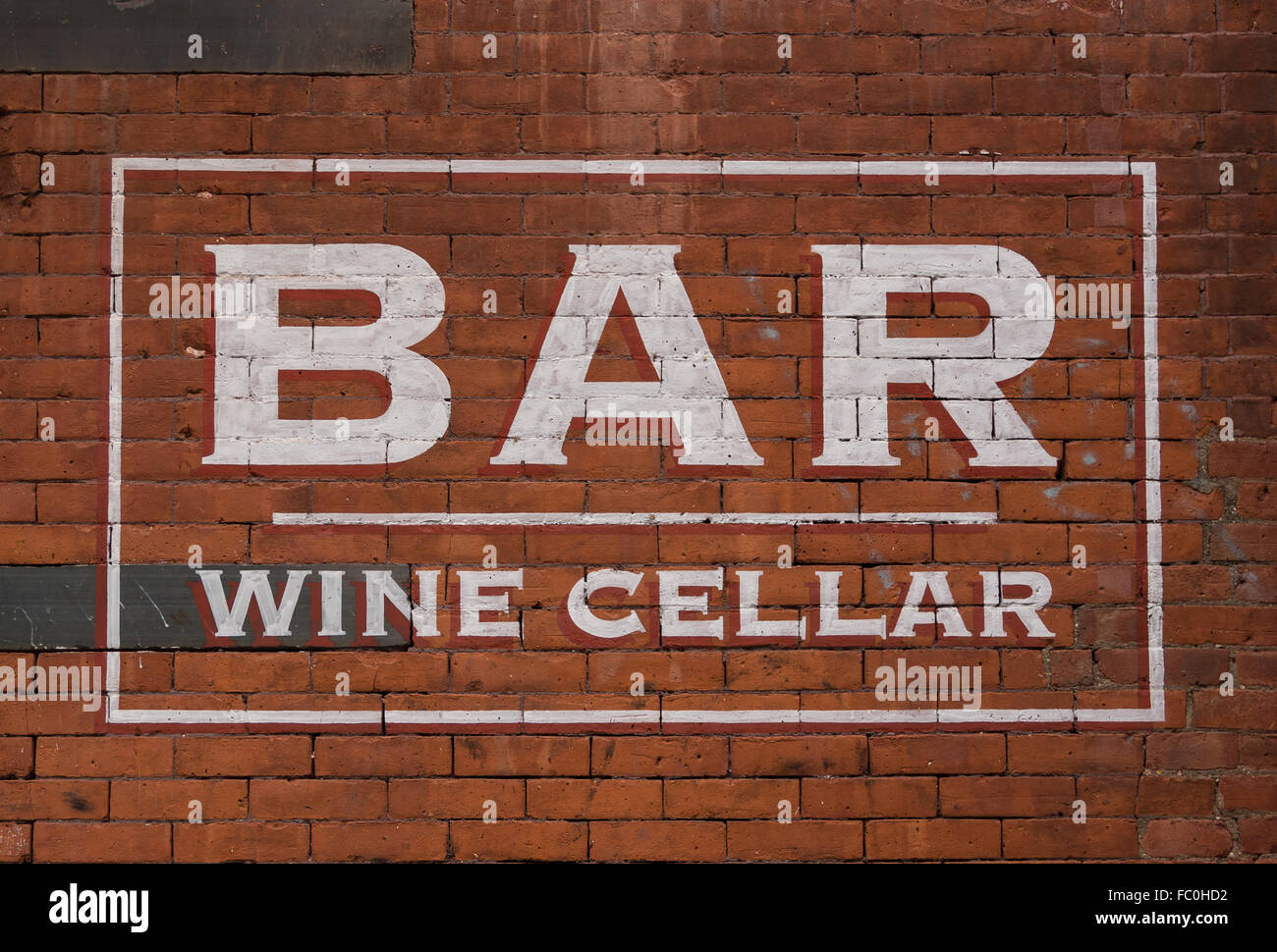 Painted sign saying Bar and Wine Cellar on a red brick wall - Stock Image