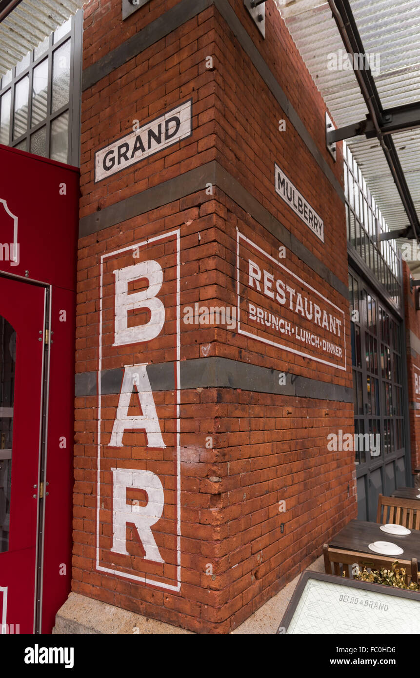 Painted bar sign on a red brick wall of Gelso and Grand bar and restaurant, corner of Grand and Mulberry street, - Stock Image