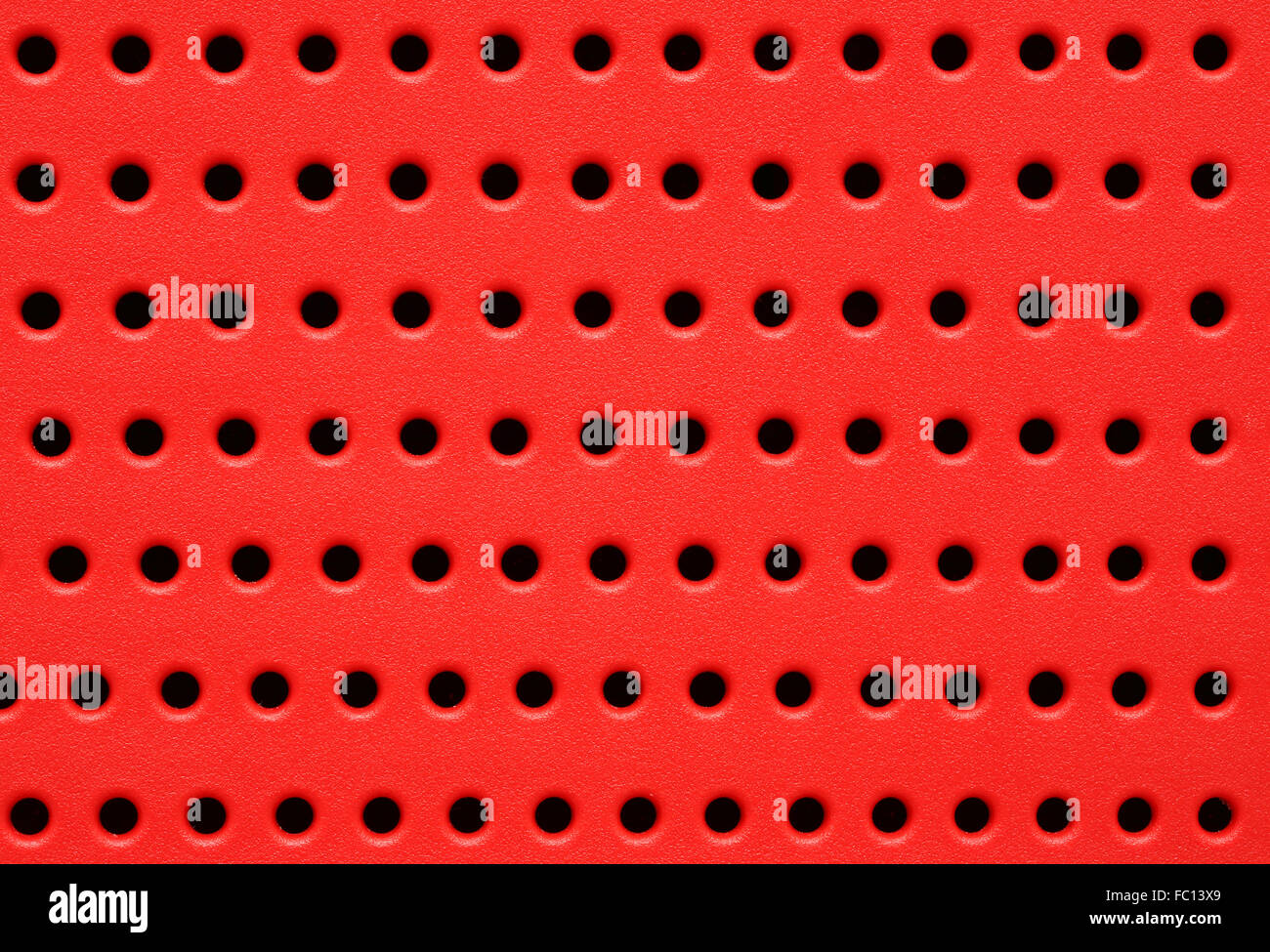 red perforated plastic background - Stock Image