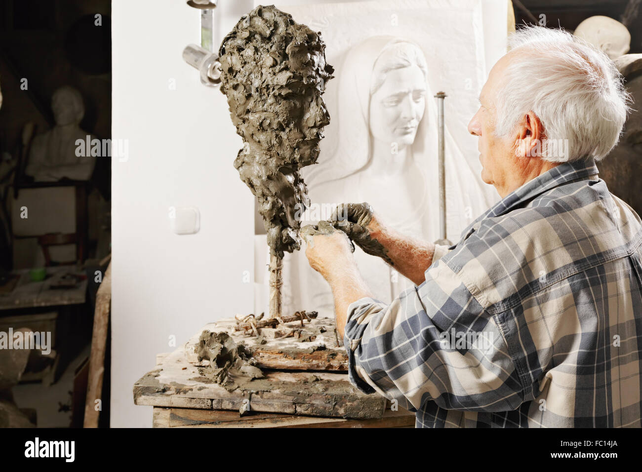 Elderly sculptor making sculpture - Stock Image