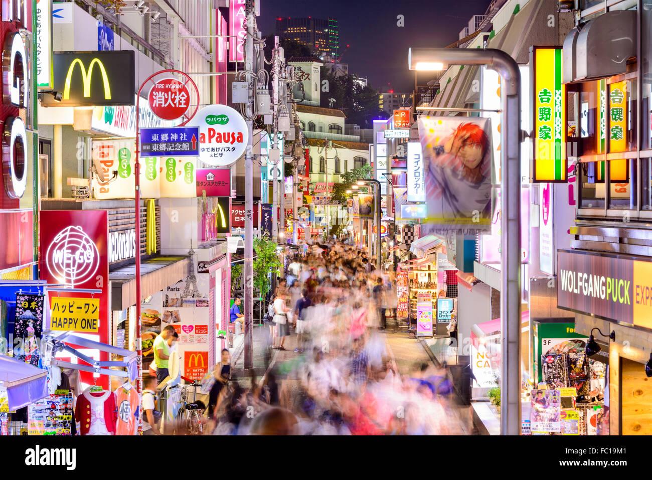 Crowds walk through Takeshita Street in the Harajuku district at night in Tokyo, Japan. - Stock Image