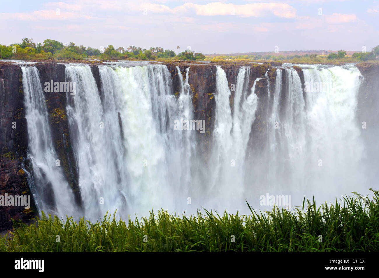 The Victoria falls is the largest curtain of water in the world (1708 meters wide). The falls and the surrounding - Stock Image
