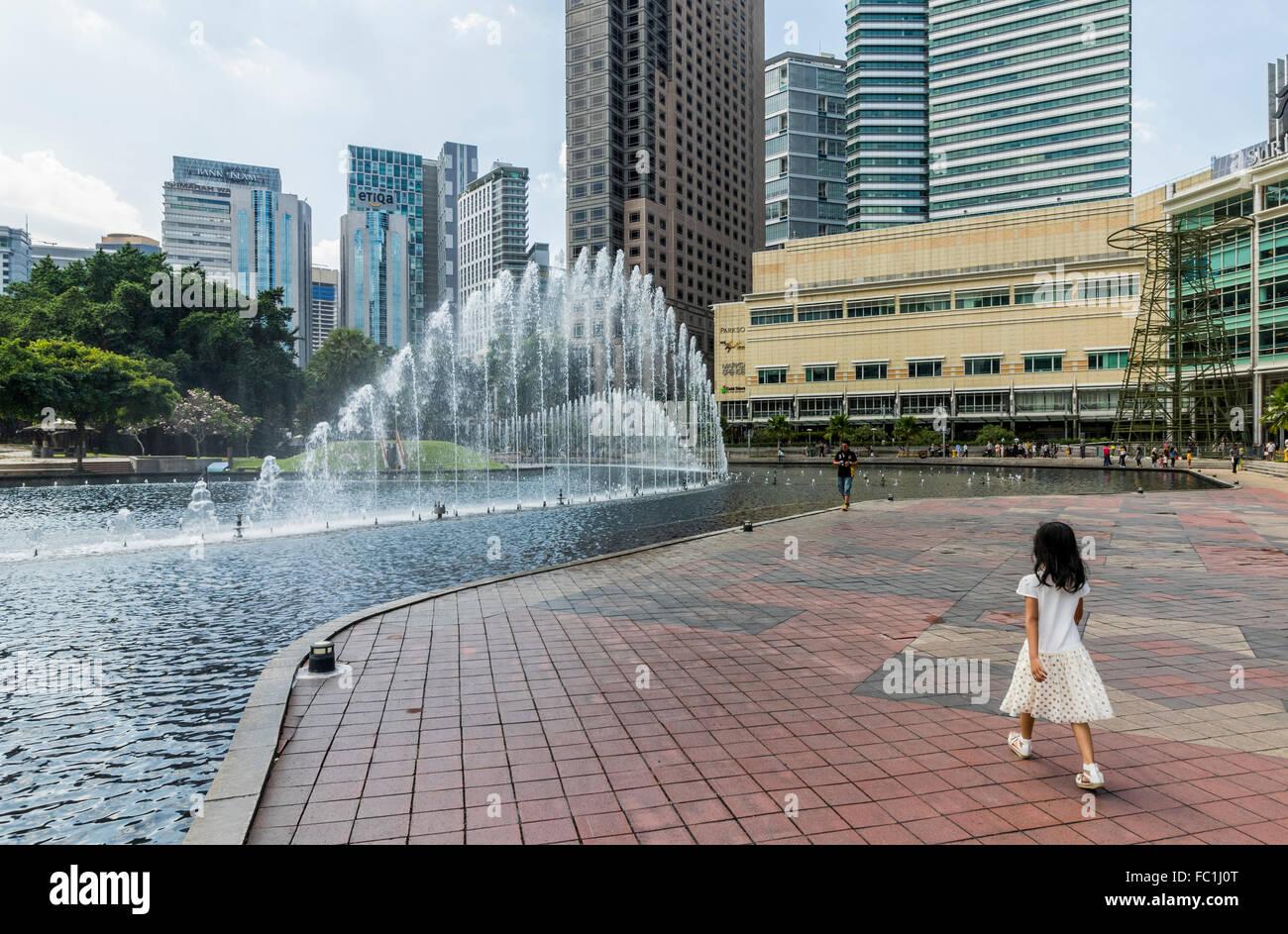 Child enjoying fountains at lake Symphony KL city centre park Kuala Lumpur Malaysia - Stock Image