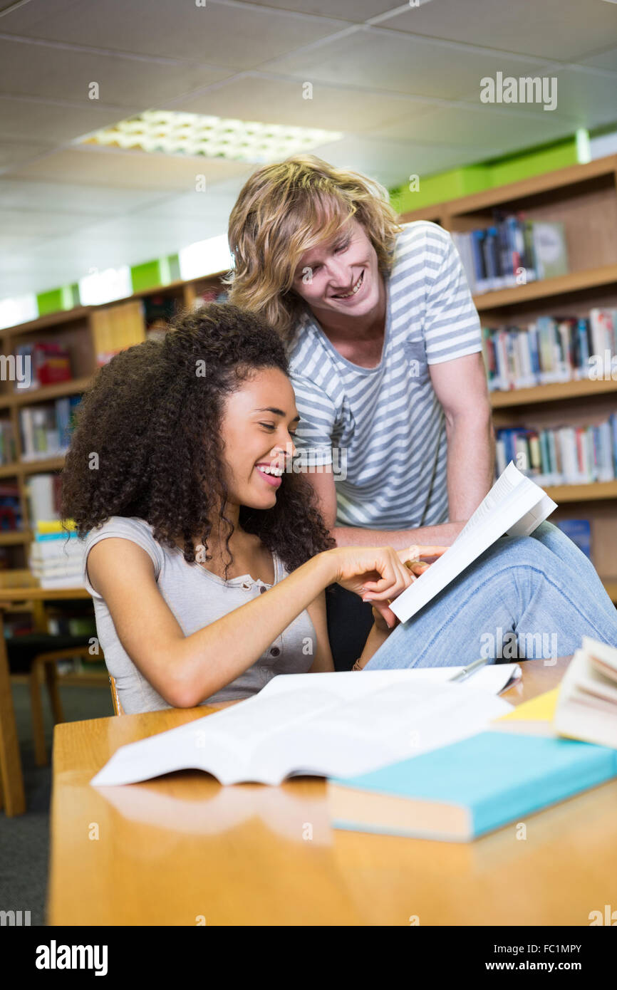 Student getting help from classmate in library - Stock Image