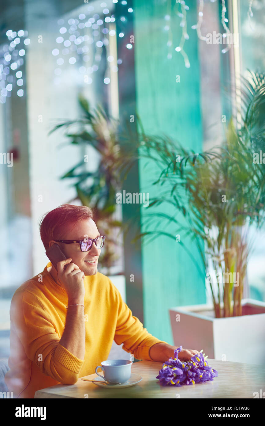 Contemporary young man calling in cafe - Stock Image