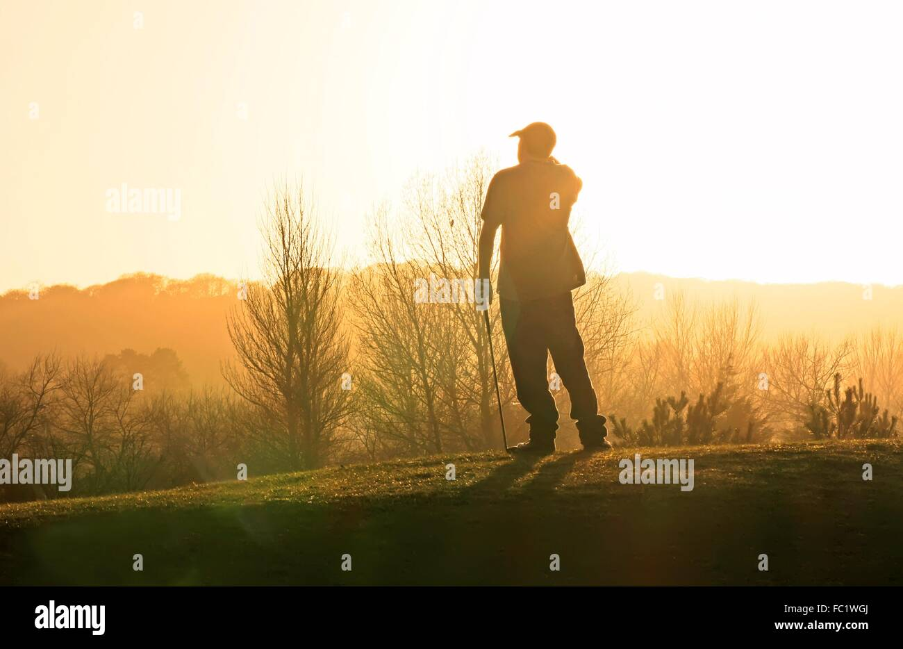 Golfer after teeing off into a sunset - Stock Image