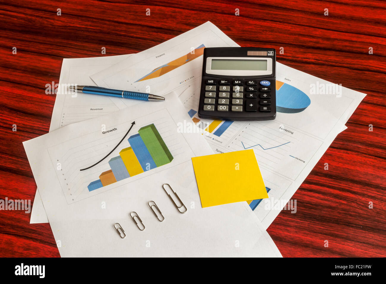 Bunch of printed charts and graphs with calculator, paper clips, yellow note and pen on them - Stock Image