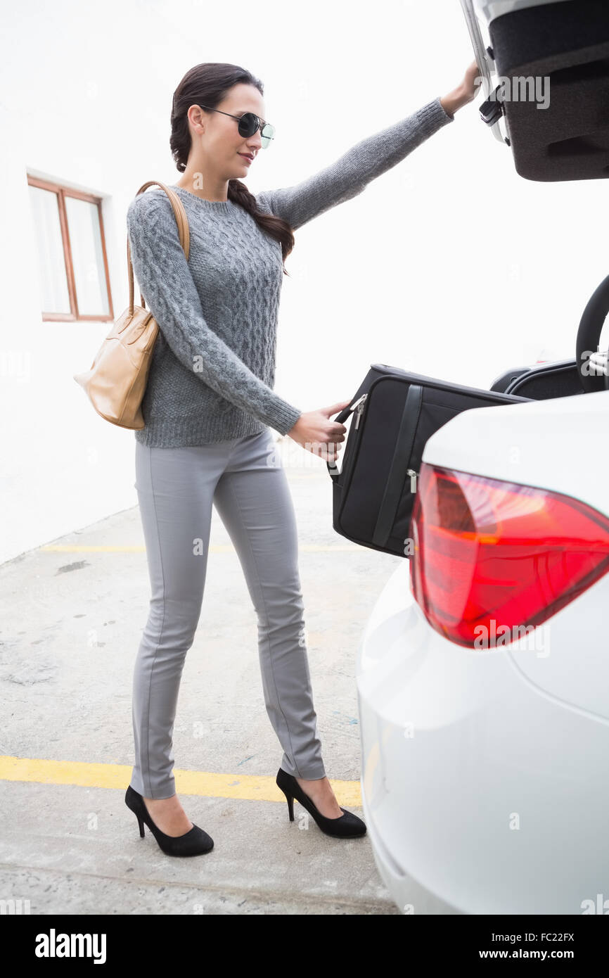 Woman pulling out a baggage of her car trunk - Stock Image