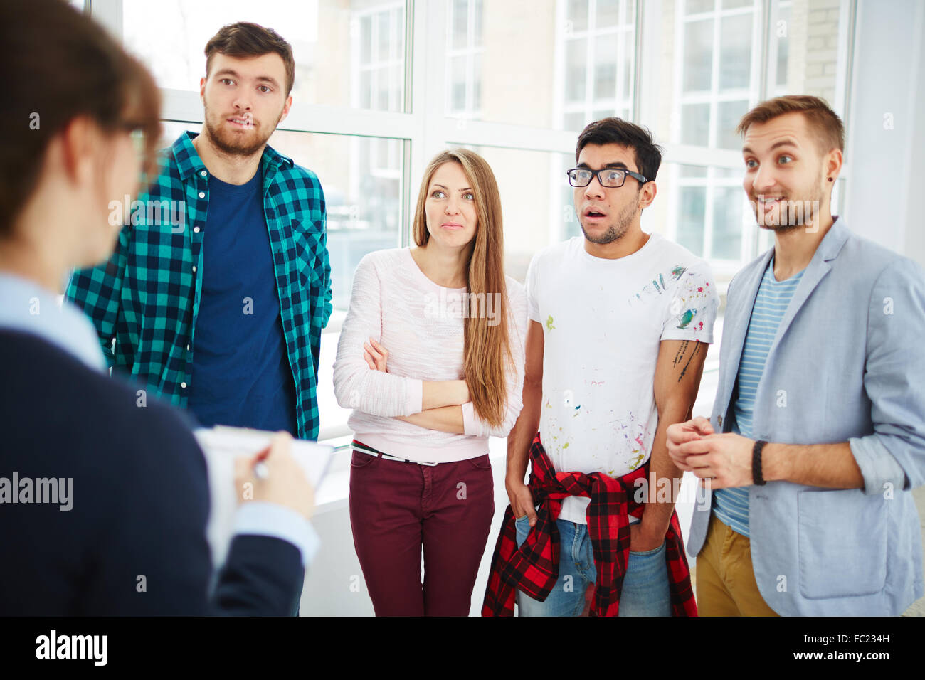 Group of astonished young people looking at their friend at psychological course - Stock Image