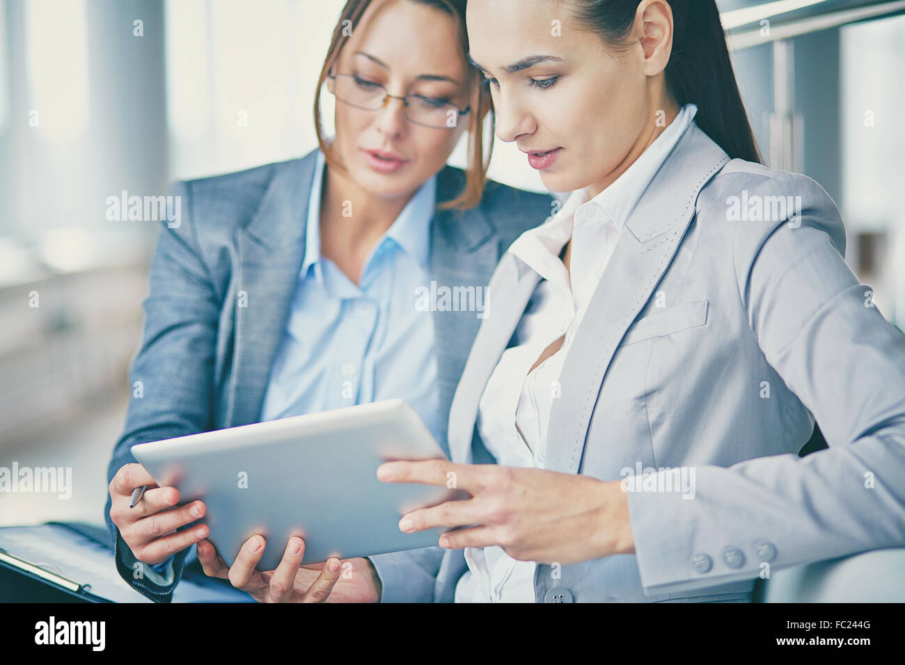 Two young businesswomen networking and discussing data - Stock Image