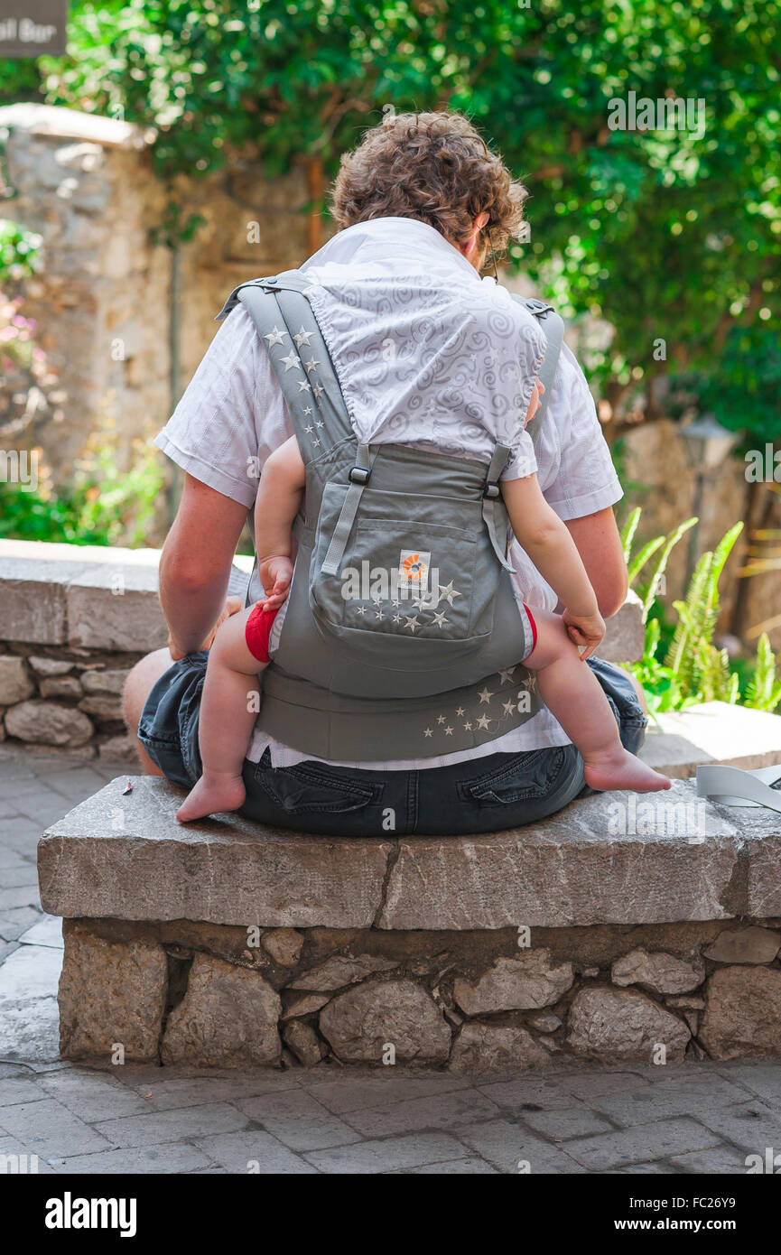 Father baby asleep, rear view of a child asleep in a harness on his father's back. - Stock Image