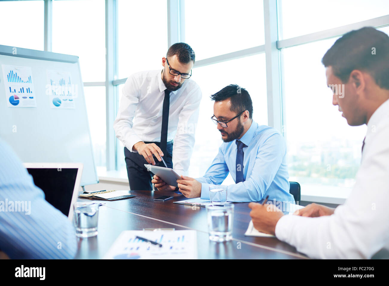 Young businessmen analyzing data in office - Stock Image