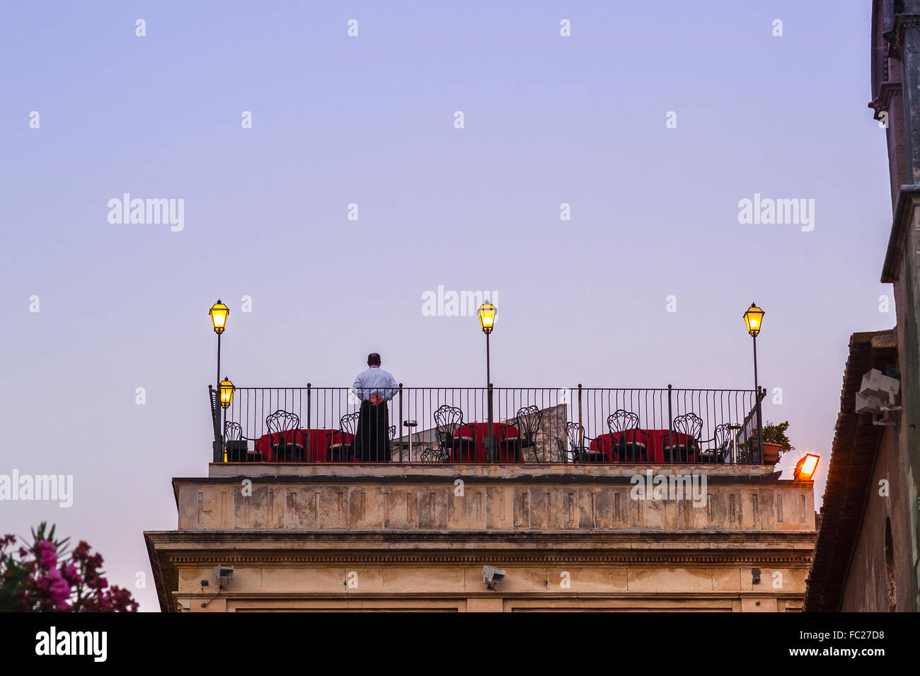 Rooftop terrace restaurant, a lone waiter stands ready for evening diners to arrive at a roof top terrace on a restaurant - Stock Image