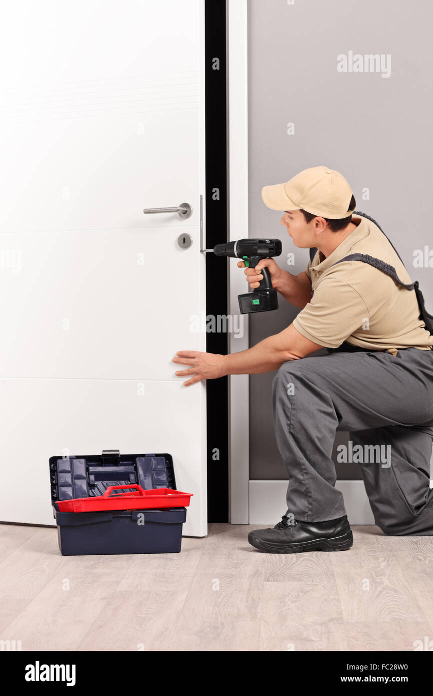 Vertical shot of a young male locksmith installing a door lock with an electric hand drill - Stock Image