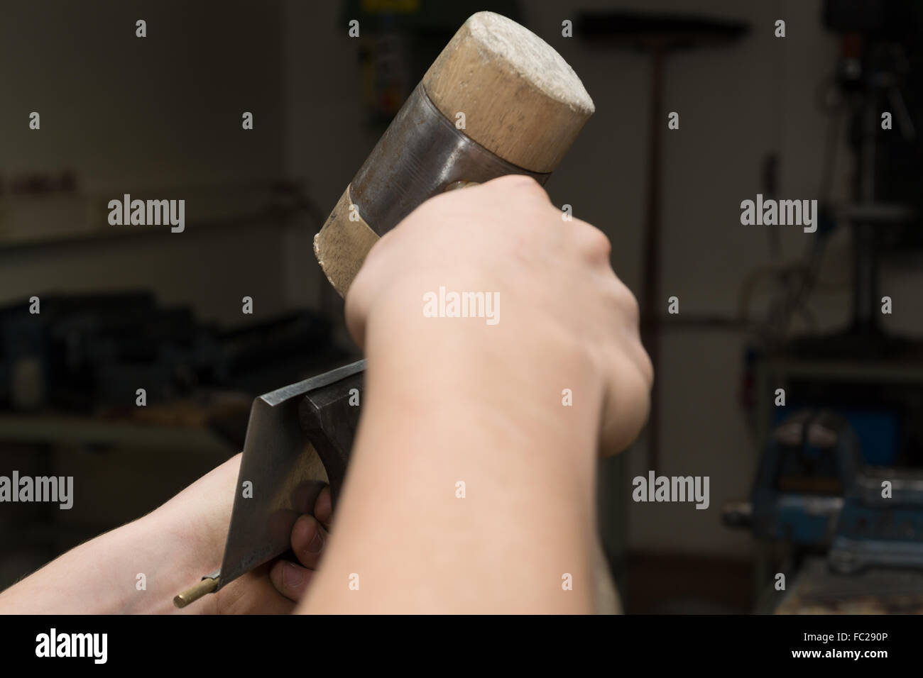 Artisan bends sheet with mallet - Stock Image