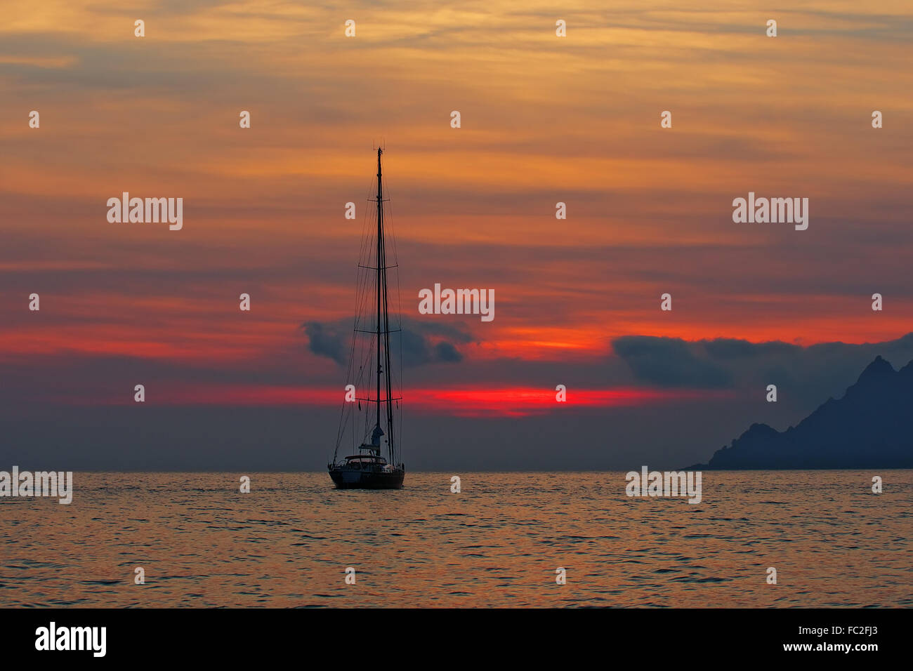 Sailing yacht in the sunset - Corsica - Stock Image
