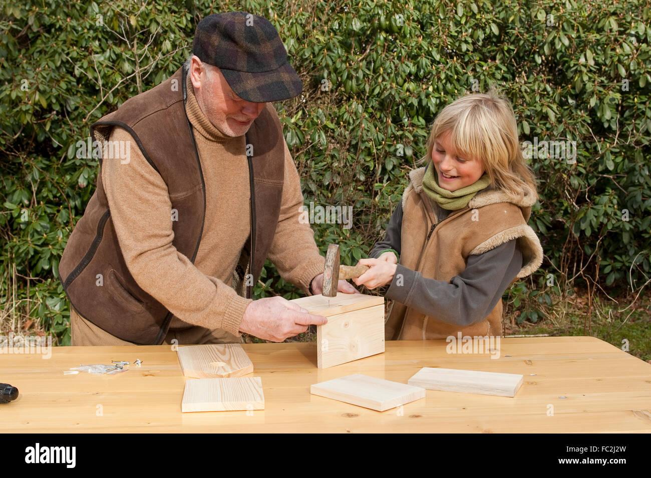 Nest box, birdhouse, building a nesting box, grandpa and grandchild, Nistkasten, Meisenkasten, Vogelnistkasten, Stock Photo