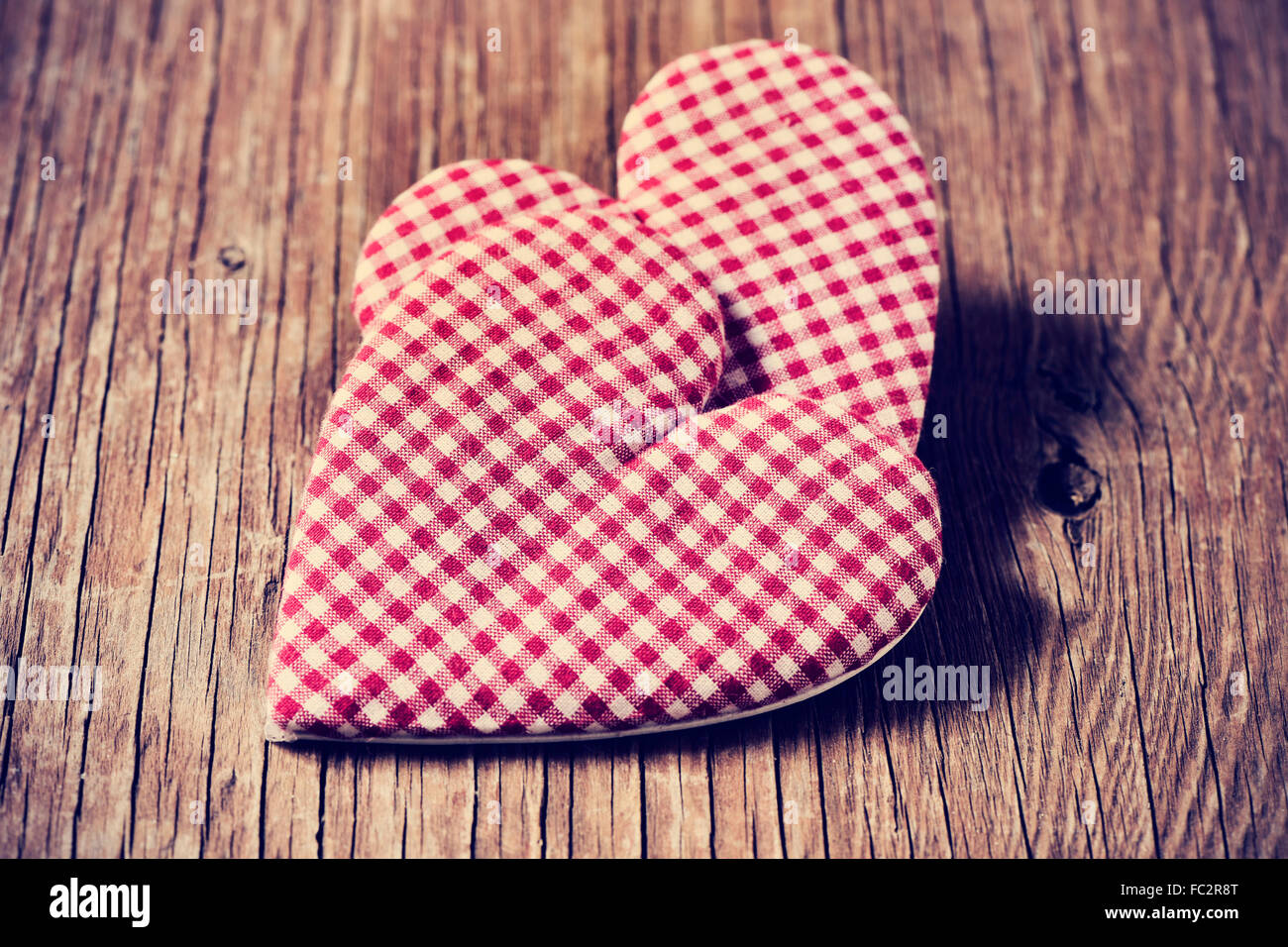 two red and white checkered hearts on a rustic wooden surface - Stock Image