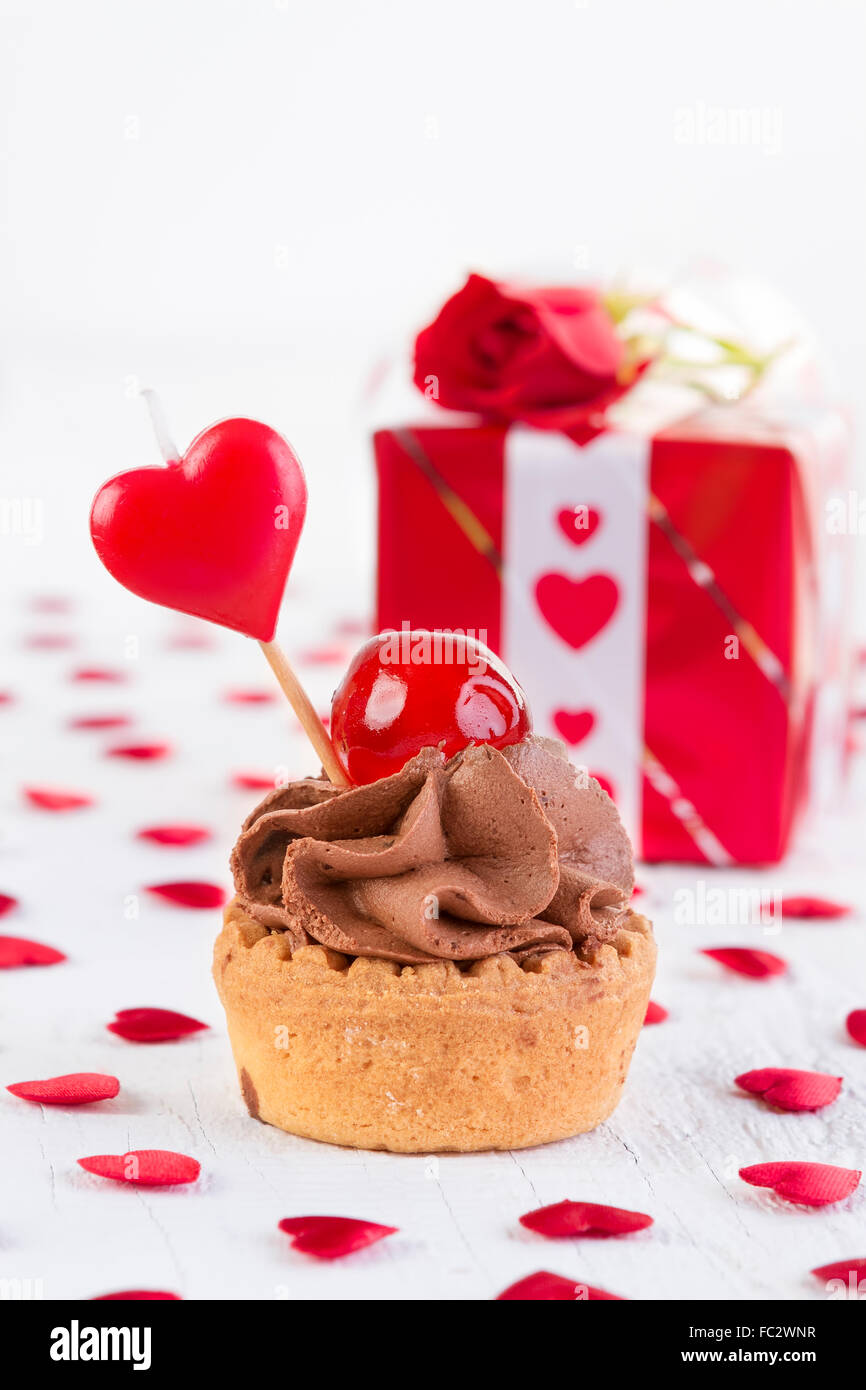Chocolate cupcake with cherry in front of gift box on white wooden background. Valentines day and love concept. - Stock Image