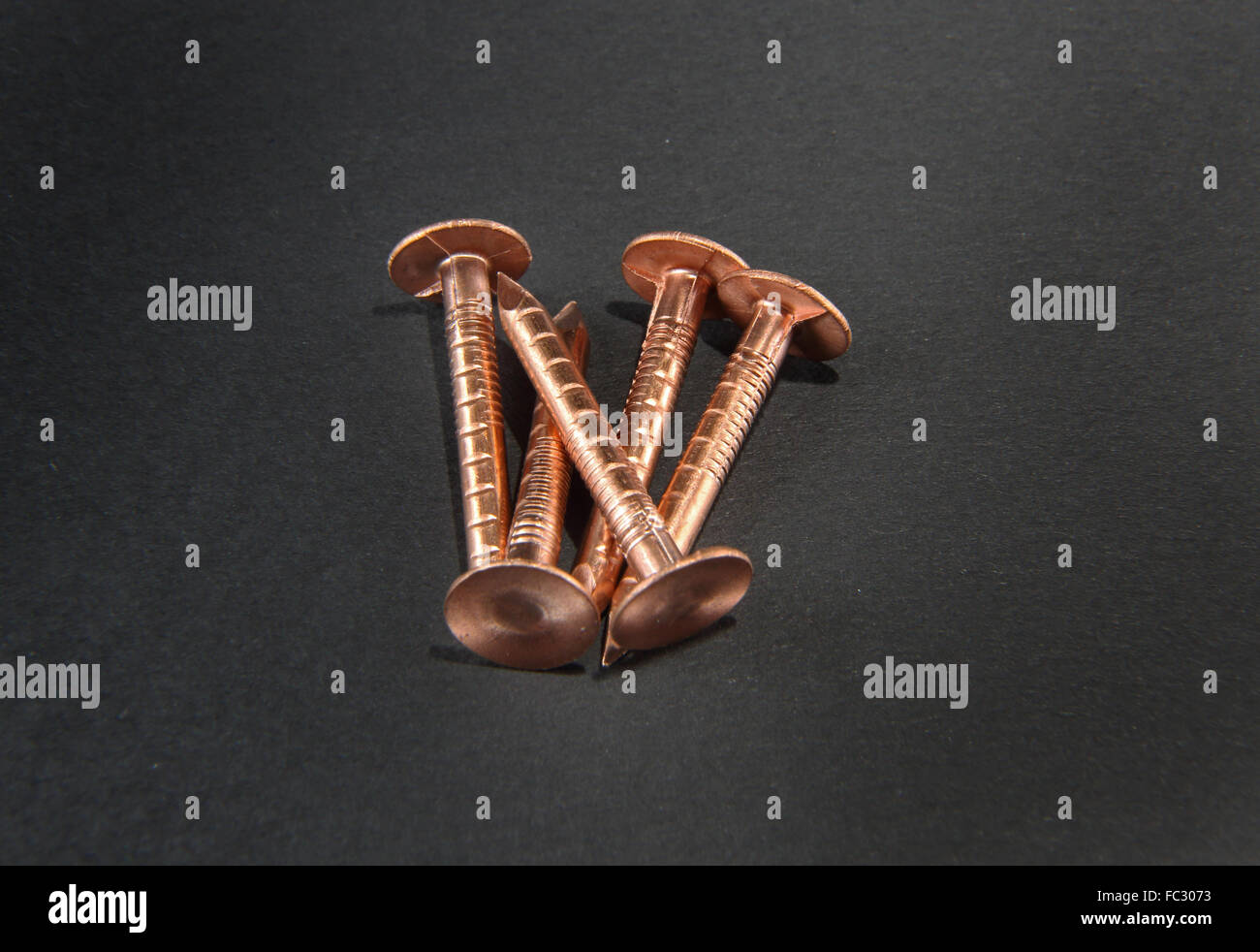 Studio close-up shot of five copper roofing nails against a black background - Stock Image