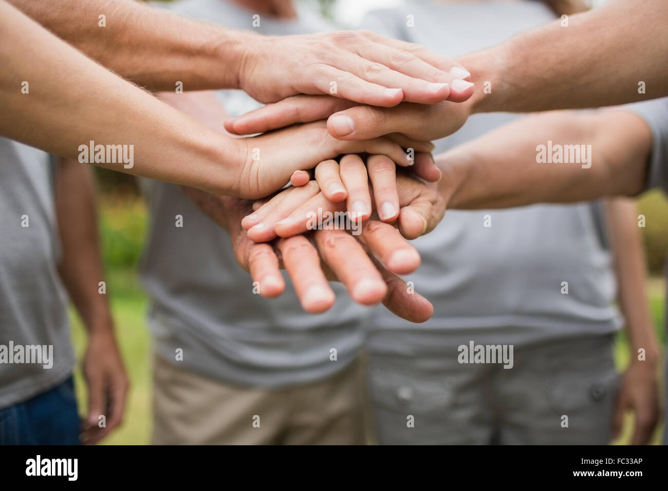 Happy volunteer family putting their hands together - Stock Image